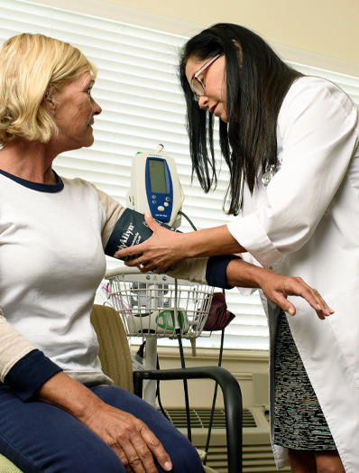 Dr. Gloria Dunking takes clients blood pressure